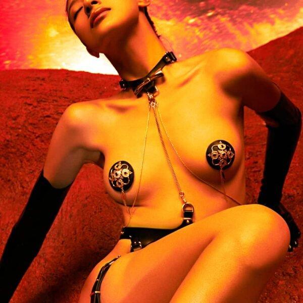 Ensemble Bondage 8 pièces de la marque Upko noir et or. Se trouve au niveau du cou un collier qui est relié à la ceinture par une chaîne en or. Le haut ne recouvre pas les seins. De part et d'autre, se trouvent des chaines couleur or qui relient le haut et le bas en diagonale. Le bas est noir et le haut des cuisses est ceinturé.