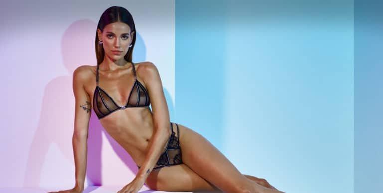 Collection Manhattan de Bracli. Ensemble de la marque Bracli avec un soutien noir à dentelle et transparent au niveau des seins, une culotte noire également en dentelle et transparente sur le devant. Le mannequin est assis et regarde droit devant l'objectif. Le fond derrière elle est rosé et blanc avec quelques reflets bleutés.